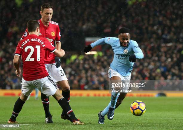 Raheem Sterling goes past Ander Herrera and Nemanja Matic of Manchester United during the Premier League match between Manchester United and...