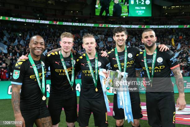 Raheem Sterling Kevin De Bruyne Oleksandr Zinchenko John Stones and Kyle Walker of Manchester City pose with the trophy following their sides victory...