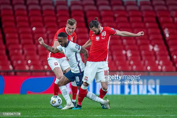 Raheem Sterling of England and Grzegorz Krychowiak and Michal Helik of Poland in action during the FIFA World Cup 2022 Qatar qualifying match between...