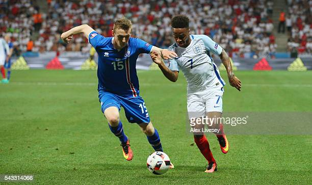 Raheem Sterling of England and Jon Dadi Bodvarsson of Iceland compete for the ball during the UEFA EURO 2016 round of 16 match between England and...