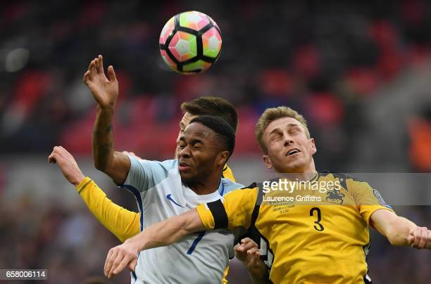 Raheem Sterling of England and Vaidas Slavickas of Lithuania battle for the ball during the FIFA 2018 World Cup Qualifier between England and...
