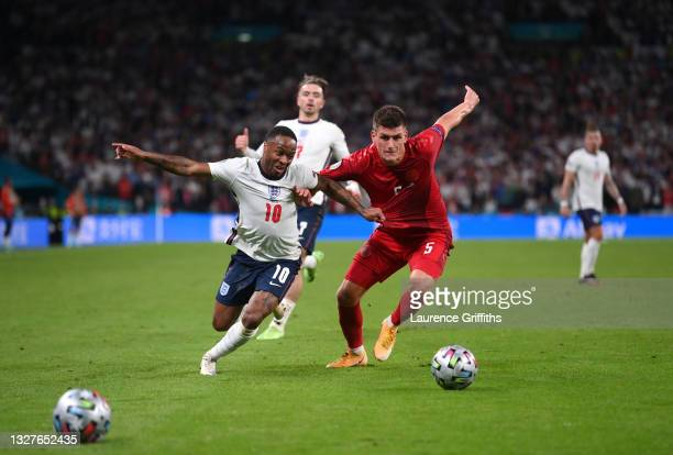 Raheem Sterling of England battles for possession Joakim Maehle of Denmark in the lead up to the penalty with a spare ball on the pitch during the...