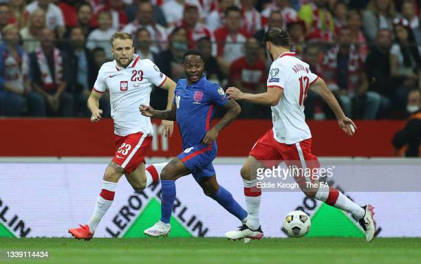 Raheem Sterling of England battles for possession with Grzegorz Krychowiak and Tymoteusz Puchacz of Poland during the 2022 FIFA World Cup Qualifier...