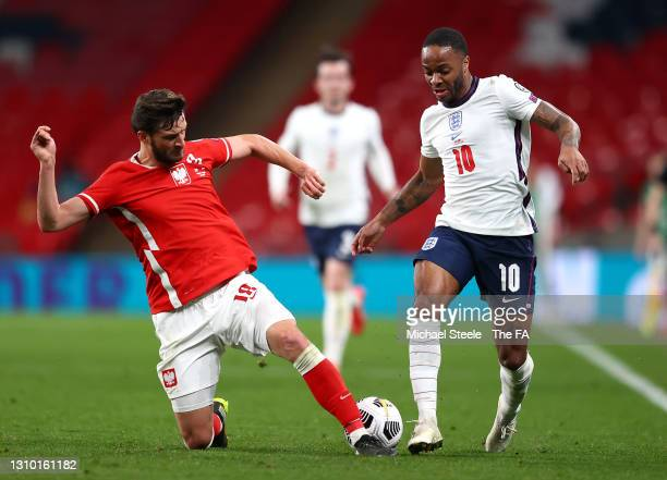 Raheem Sterling of England is challenged by Bartosz Bereszynski of Poland during the FIFA World Cup 2022 Qatar qualifying match between England and...