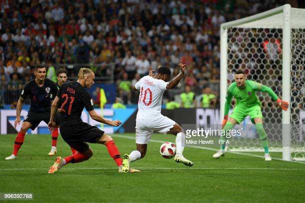 Raheem Sterling of England is challenged by Domagoj Vida of Croatia inside the penalty area during the 2018 FIFA World Cup Russia Semi Final match...