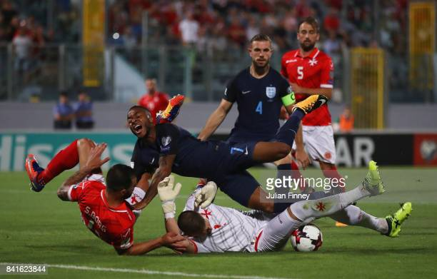 Raheem Sterling of England is challenged by Steve Borg and Andrew Hogg of Malta during the FIFA 2018 World Cup Qualifier between Malta and England at...