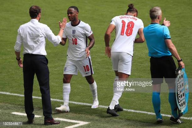 Raheem Sterling of England is greeted by Gareth Southgate, Head Coach of England as Raheem Sterling is substituted off and Dominic Calvert-Lewin of...