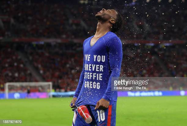 Raheem Sterling of England is hit by a cup thrown from the crowd as he celebrates after scoring their team's first goal wearing a t-shirt that reads...