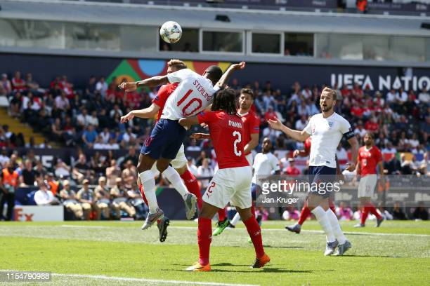 Raheem Sterling of England is pushed from behind by Kevin Mbabu of Switzerland during the UEFA Nations League Third Place Playoff match between...