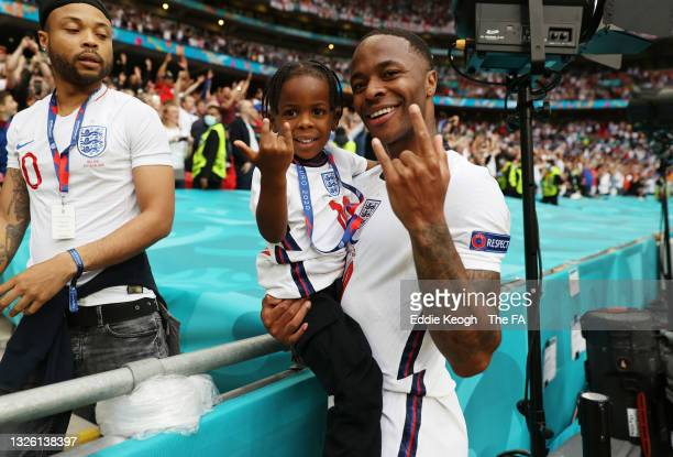 Raheem Sterling of England poses for a photo with his child following victory in the UEFA Euro 2020 Championship Round of 16 match between England...