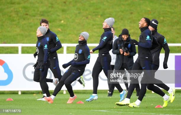 Raheem Sterling of England reacts as he takes part in a training drill with Kieran Trippier, Ben Chilwell and Callum Wilson during the England...