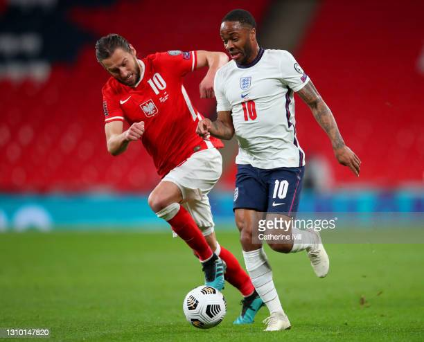 Raheem Sterling of England runs with the ball whilst under pressure from Grzegorz Krychowiak of Poland during the FIFA World Cup 2022 Qatar...