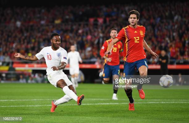 Raheem Sterling of England scores his team's first goal as Marcos Alonso of Spain looks on during the UEFA Nations League A Group Four match between...