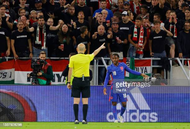 Raheem Sterling of England talks to referee Cuneyt Cakır during the 2022 FIFA World Cup Qualifier match between Hungary and England at Stadium Puskas...