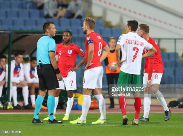 Raheem Sterling of England watches as captain Harry Kane speaks with referee Ivan Bebek during the UEFA Euro 2020 qualifier between Bulgaria and...