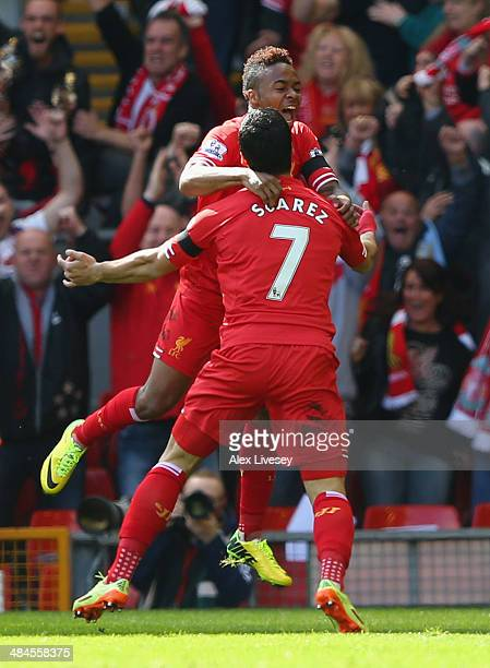 Raheem Sterling of Liverpool celebrates scoring the first goal with Luis Suarez during the Barclays Premier League match between Liverpool and...