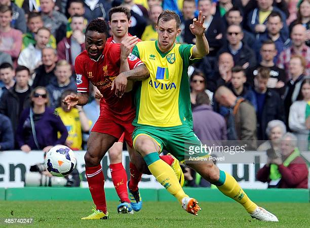 Raheem Sterling of Liverpool competes with Steven Whittaker of Norwich during the Barclays Premier League match between Norwich City and Liverpool at...