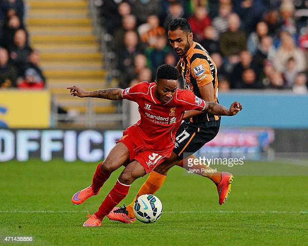 Raheem Sterling of Liverpool goes up with Ahmed Elmohamady of Hull City during the Barclays Premier League match between Hull City and Liverpool at...