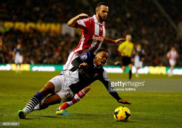Raheem Sterling of Liverpool is fouled by Marc Wilson of Stoke City for a penalty kick during the Barclays Premier League match between Stoke City...