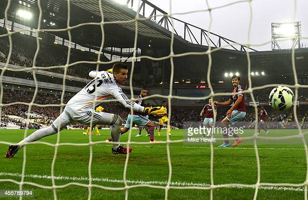 Raheem Sterling of Liverpool scores his team's first goal past goalkeeper Adrian of West Ham during the Barclays Premier League match between West...
