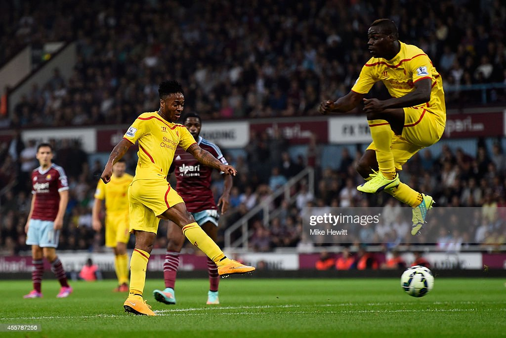 Raheem Sterling of Liverpool scores is team's first goal as teammate Mario Balotelli of Liverpool jumps to avoid the shot during the Barclays Premier League match between West Ham United and Liverpool at Boleyn Ground on September 20, 2014 in London, England.
