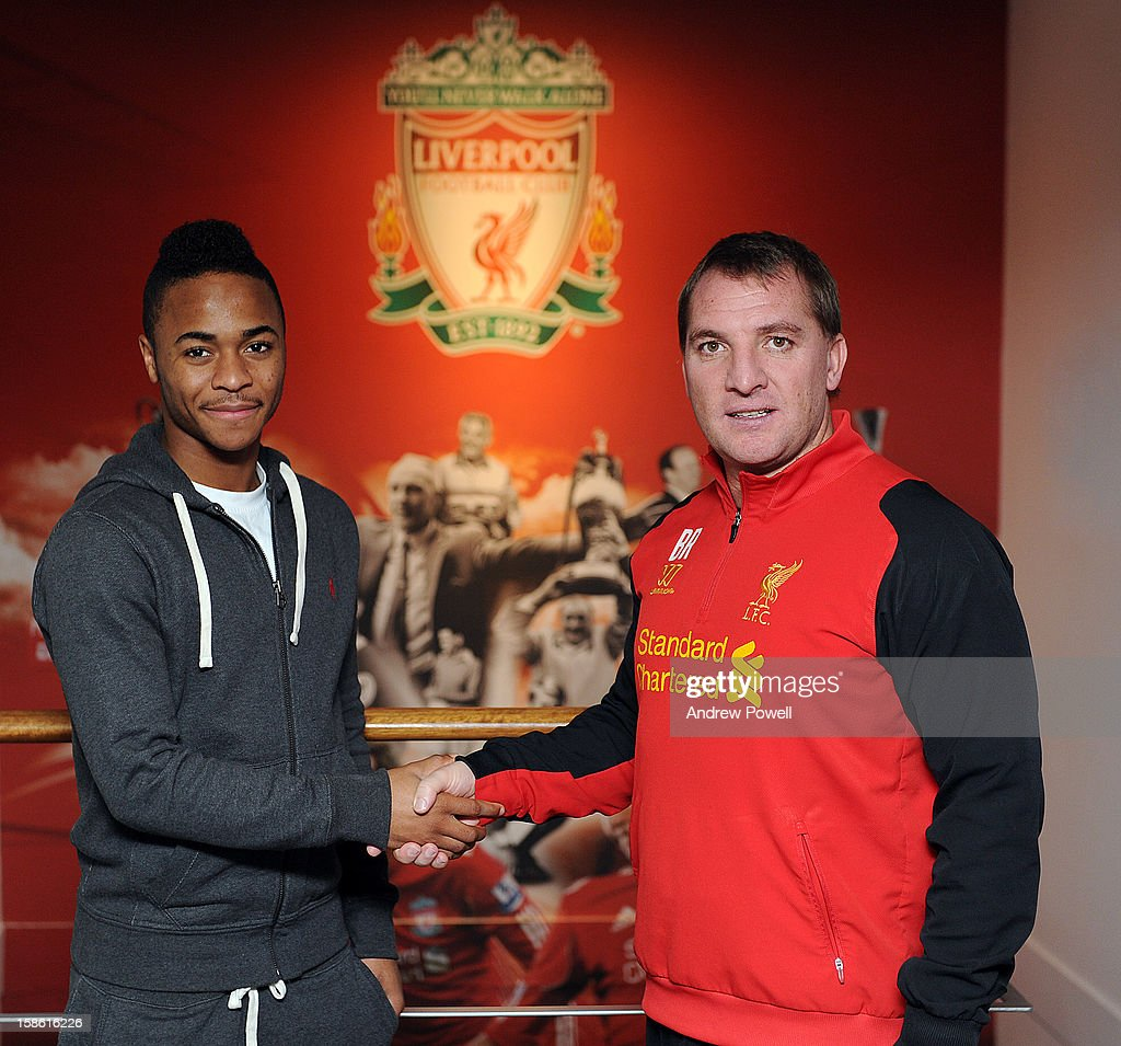 (MINIMUM USAGE FEE APPLIES - 150 GBP FOR PRINT AND GBP 75 ONLINE OR LOCAL EQUIVALENT) Raheem Sterling of Liverpool signs a new contract with Brendan Rodgers (R) manager of Liverpool FC at Melwood Training Ground on December 21, 2012 in Liverpool, England.