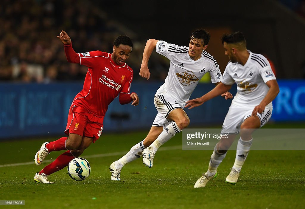 Raheem Sterling of Liverpool takes on Jack Cork and Neil Taylor of Swansea City during the Barclays Premier League match between Swansea City and Liverpool at Liberty Stadium on March 16, 2015 in Swansea, Wales.