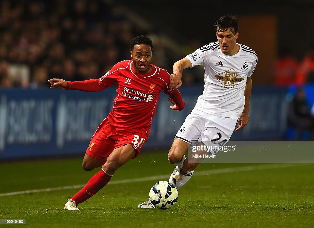 Raheem Sterling of Liverpool takes on Jack Cork of Swansea City during the Barclays Premier League match between Swansea City and Liverpool at Liberty Stadium on March 16, 2015 in Swansea, Wales.