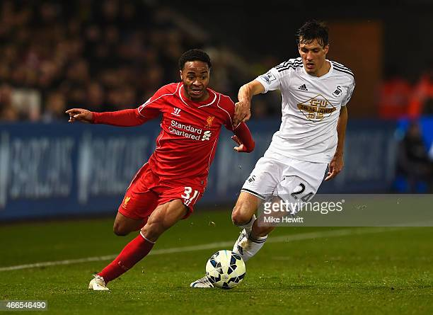 Raheem Sterling of Liverpool takes on Jack Cork of Swansea City during the Barclays Premier League match between Swansea City and Liverpool at...