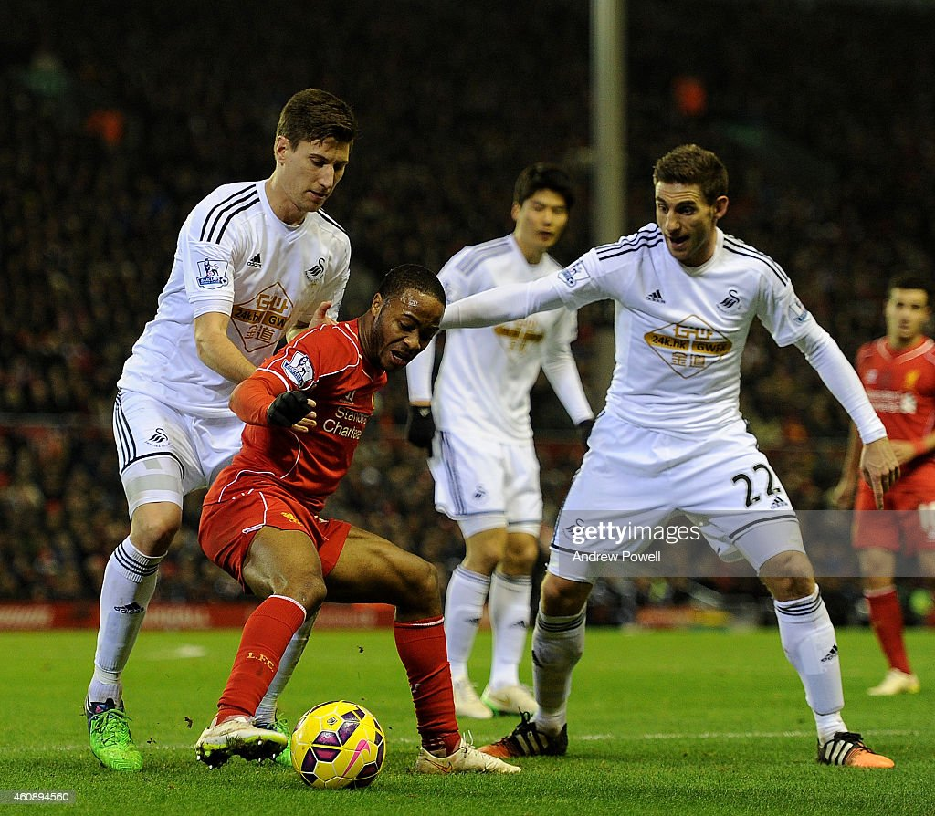 Raheem Sterling of Liverpool tussles with Federico Fernandez and Angel Rangel of Swansea City during the Barclays Premier League match between Liverpool and Swansea City at Anfield on December 29, 2014 in Liverpool, England.