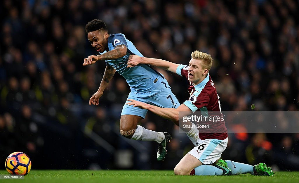 Raheem Sterling of Manchester City (L) and Ben Mee of Burnley (R) battle for possession during the Premier League match between Manchester City and Burnley at Etihad Stadium on January 2, 2017 in Manchester, England.