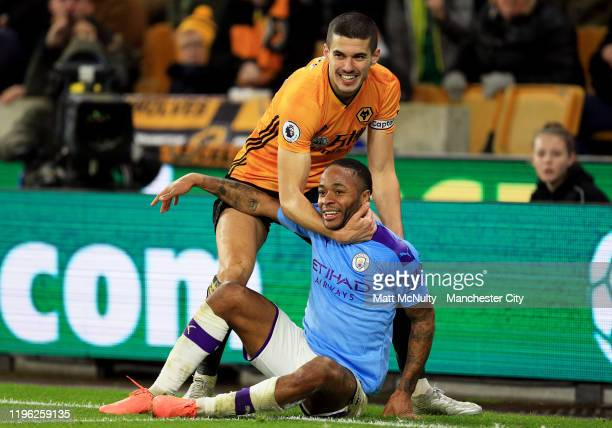 Raheem Sterling of Manchester CIty and Conor Coady of Wolverhampton Wanderers share a joke during the Premier League match between Wolverhampton...