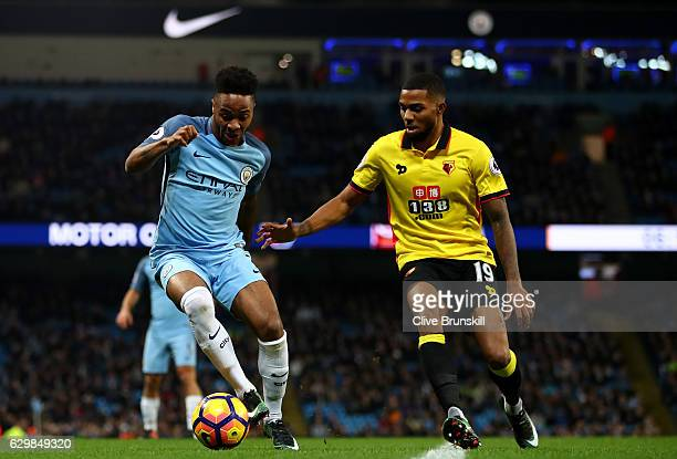 Raheem Sterling of Manchester City and Jerome Sinclair of Watford compete for the ball during the Premier League match between Manchester City and...