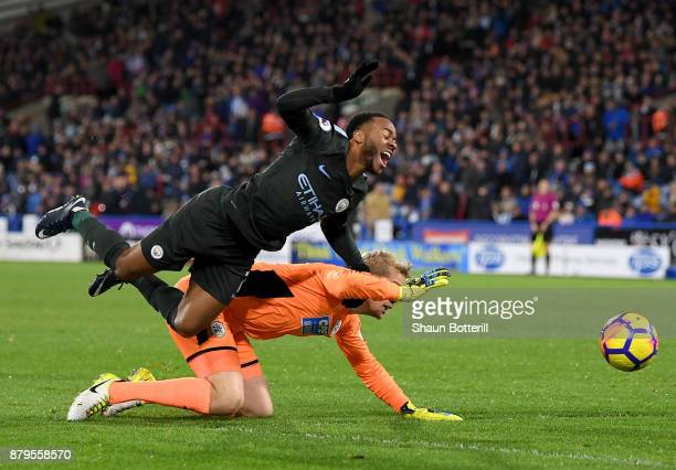 Raheem Sterling of Manchester City and Jonas Lossl of Huddersfield Town clash during the Premier League match between Huddersfield Town and...