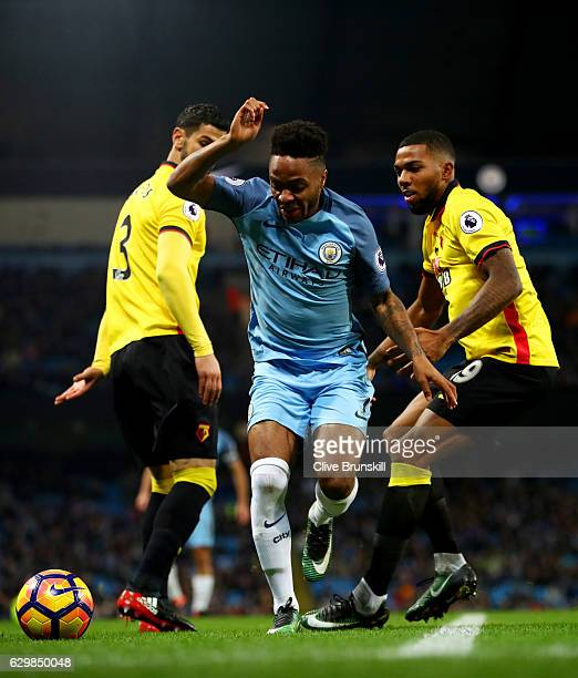 Raheem Sterling of Manchester City attempts to take the ball past Jerome Sinclair of Watford during the Premier League match between Manchester City...