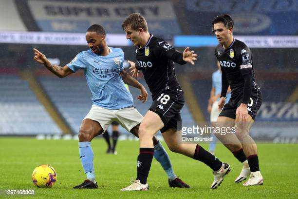 Raheem Sterling of Manchester City battles for possession with Matt Targett and Jack Grealish of Aston Villa during the Premier League match between...