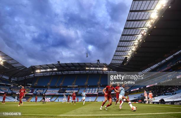 Raheem Sterling of Manchester City battles for possession with Trent Alexander-Arnold of Liverpool as fans watch on the big screen during the Premier...