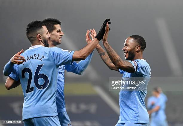 Raheem Sterling of Manchester City celebrates after scoring his sides fifth goal with team-mates Riyad Mahrez and Joao Cancelo during the Premier...