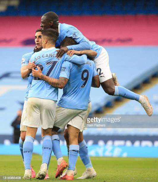 Raheem Sterling of Manchester City celebrates with Benjamin Mendy and team mates after scoring their side's first goal during the Premier League...