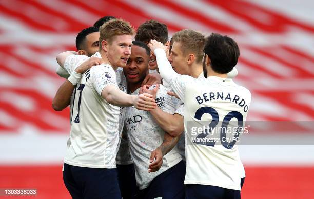 Raheem Sterling of Manchester City celebrates with Kevin De Bruyne and Bernardo Silva after scoring his team's first goal during the Premier League...