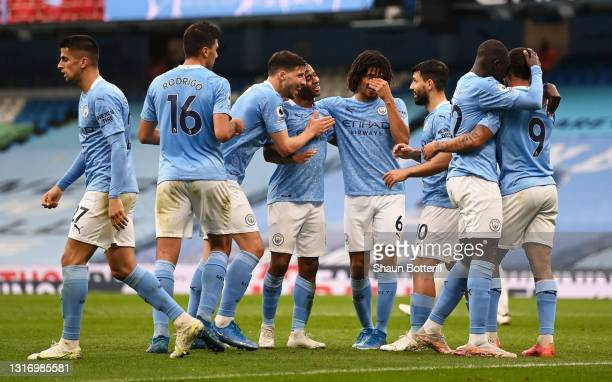 Raheem Sterling of Manchester City celebrates with Ruben Dias, Sergio Aguero and team mates after scoring their side's first goal during the Premier...