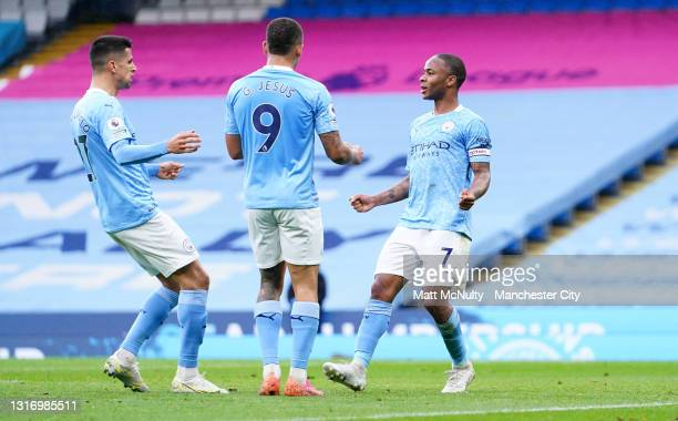 Raheem Sterling of Manchester City celebrates with team mates Joao Cancelo and Gabriel Jesus after scoring their side's first goal during the Premier...