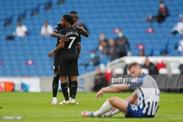 Raheem Sterling of Manchester City celebrates with teammate Benjamin Mendy after scoring his team's first goal during the Premier League match...