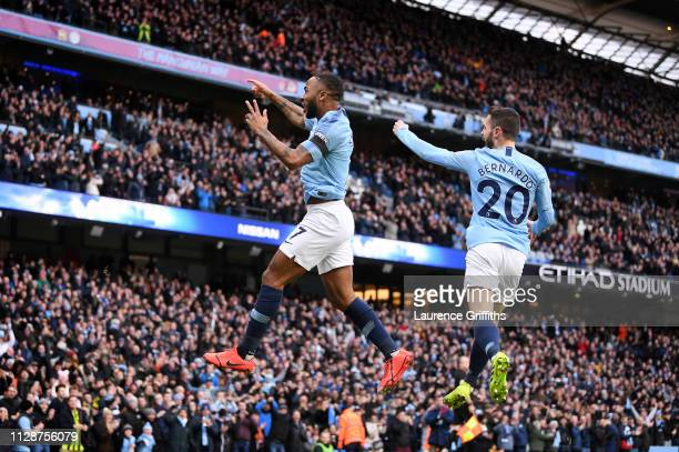 Raheem Sterling of Manchester City celebrates with teammate Bernardo Silva after scoring his team's first goal during the Premier League match...