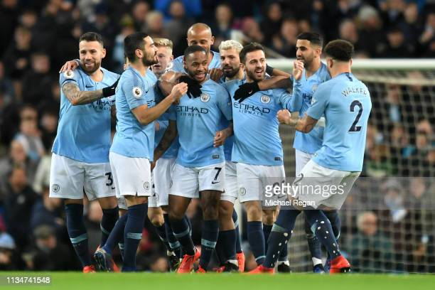 Raheem Sterling of Manchester City celebrates with teammates after scoring his team's first goal during the Premier League match between Manchester...