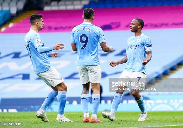 Raheem Sterling of Manchester City celebrates with teammates after scoring his teams first goal during the Premier League match between Manchester...