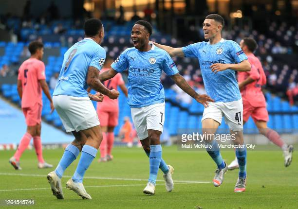 Raheem Sterling of Manchester City celebrates with teammates Gabriel Jesus and Phil Foden after scoring his team's first goal during the UEFA...