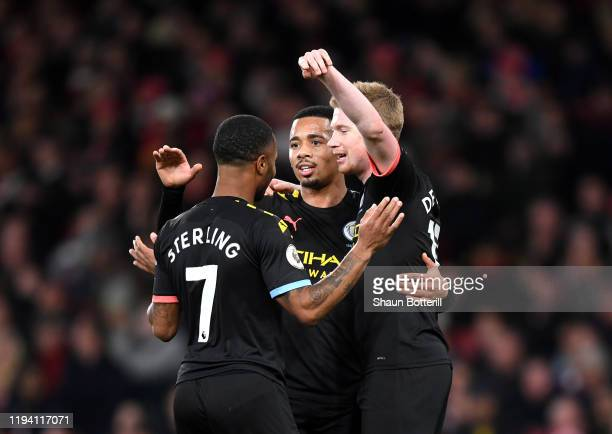 Raheem Sterling of Manchester City celebrates with teammates Kevin De Bruyne and Gabriel Jesus after scoring his team's second goal during the...