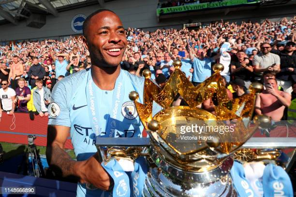 Raheem Sterling of Manchester City celebrates with the Premier League Trophy after winning the title following the Premier League match between...