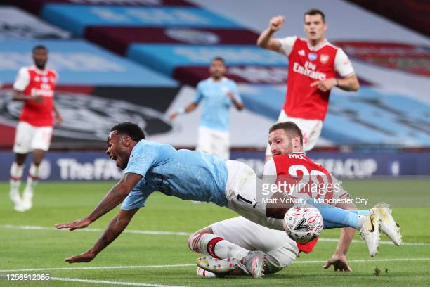 Raheem Sterling of Manchester City clashes with Shkodran Mustafi of Arsenal during the FA Cup Semi Final match between Arsenal and Manchester City at...